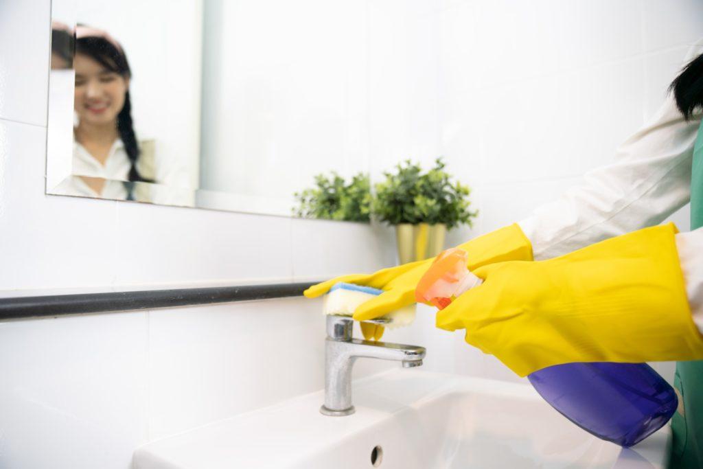 Trucos limpieza baño mujer con guantes limpiando lavabo baño