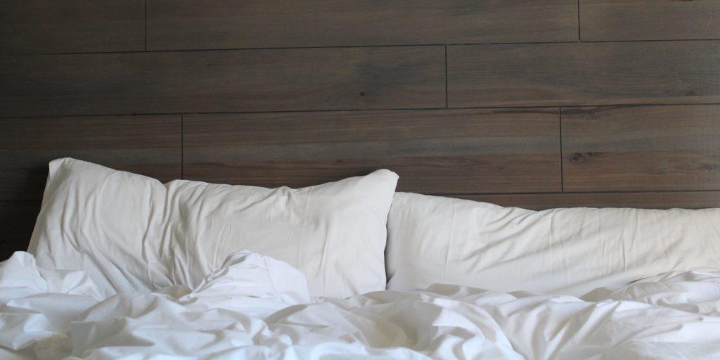 limpiar almohada plumas y quitar mal olor - cama con almohadas blancas
